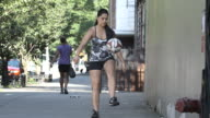 A young ethnic woman dribbles a soccer ball on a quiet Brooklyn block - slow motion - 4k