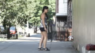 A young, ethnic woman plays soccer in the streets of Brooklyn - slow motion - 4k