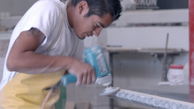 CU young factory worker in fast motion  whipping up and down polishes the rounded bull nose edge of marble countertop piece with his power sander tool  / Thousand Palms, California, USA