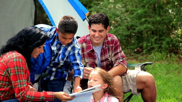 Young family camping outdoors in tent.  National forest. Woods.