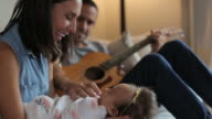 Young family enjoy musical moments in living room