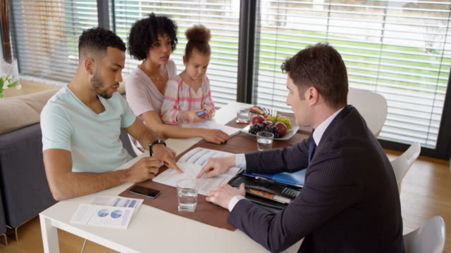 Young family having a meeting with a personal banker in their house