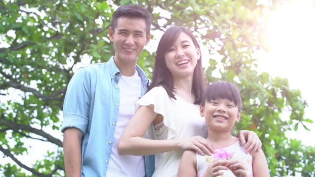 MS young family together in a park