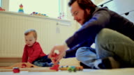 Young father and son playing at home