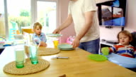 Young Father is Setting the Table for his Children