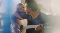 MS. Young father plays acoustic guitar for his daughter as she leans on his shoulder and smiles.