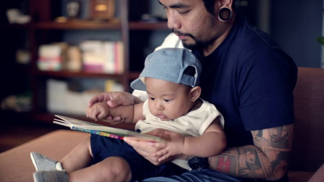 Young father reading with his baby boy