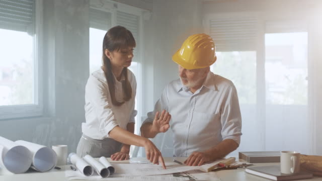 Young female architects and senior construction worker