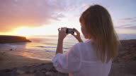 Young female at beach taking pictures of sunset with phone