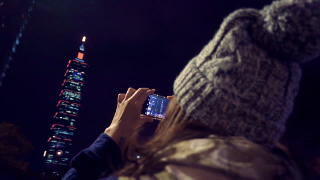 Young female at Taiwan taking pictures of Taipei Tower with smartphone
