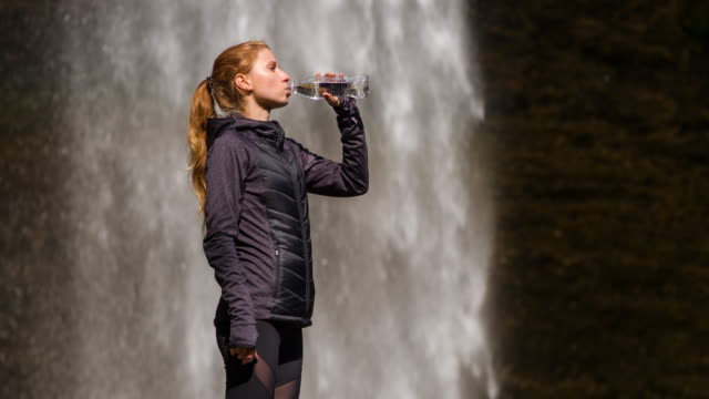 Young female athlete drinking water in front of a waterfall