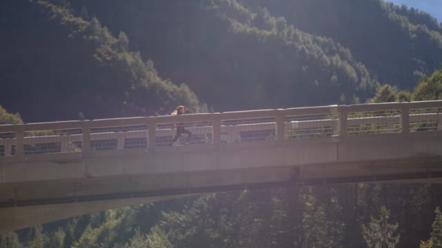 Young female athlete running on a concrete bridge