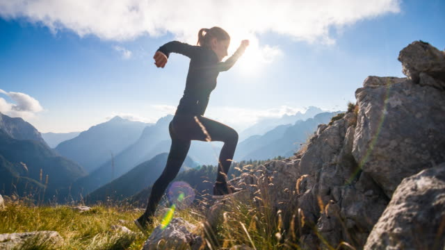 Young female athlete running up the mountain