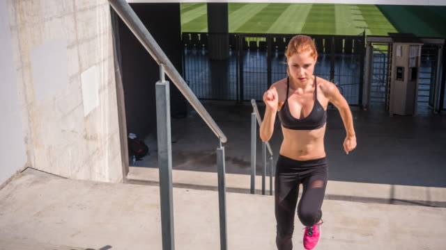 Young female athlete running up the stairs of a stadium