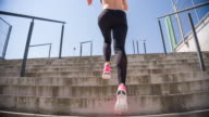 Young female athlete running up the stairs