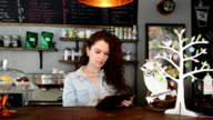 Young female barista using a digital tablet