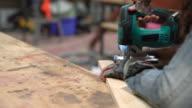 Young female carpenter cutting wood
