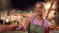 CU, Young female cashier at garden center receiving credit card, Cambria, California, USA
