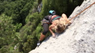Young female climber ascends vertical rock, above forest
