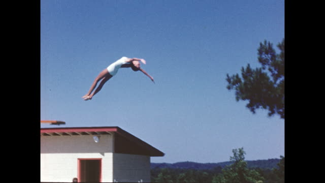 A young female competitive diver does a backflip into a pool.