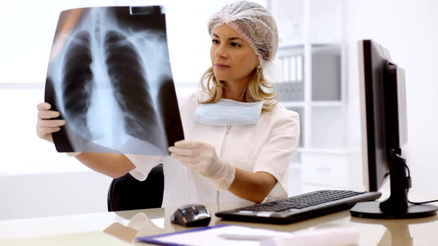 Young female doctor examining a  x-ray image.