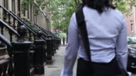 Young female executive leaving brownstone, walking on city street, to go to the office.
