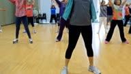 Unga kvinnliga instruktör leder yogapass för seniorer