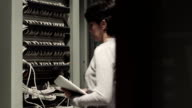 Young female IT engineer working on datacenter servers
