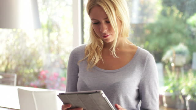 Young female looking at ipad and drinking tea in kitchen
