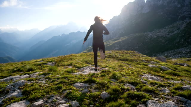 Young female runner running on top of a mountain