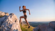 Young female runner running uphill a rocky landscape