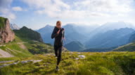 Young female runner training in the mountains