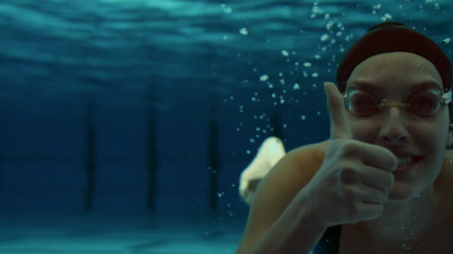 Young female swimmer showing thumbs up