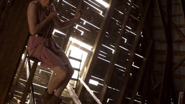 Young female swinging in a barn