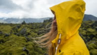 Young female tourist admiring Iceland's mossy landscape