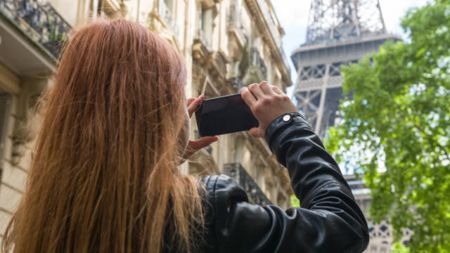 Young female tourist walking the streets of Paris and taking pictures of Eiffel Tower