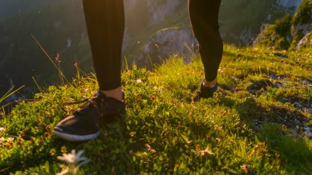 Ung kvinna går på en äng i bergen