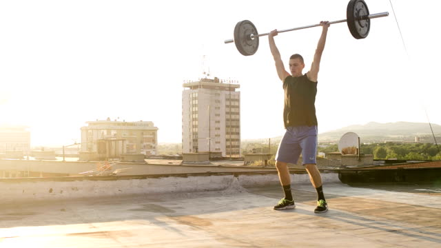 Young fit athlete man doing Clean and Jerk
