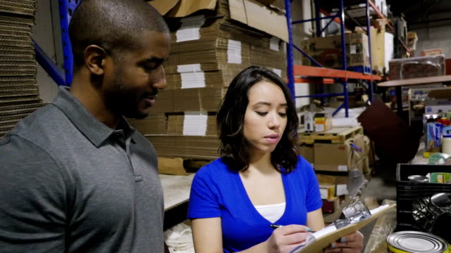 Young food bank manager taking inventory of donated groceries with volunteer in warehouse