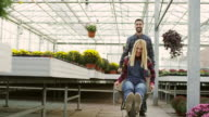 Young funny couple in greenhouse