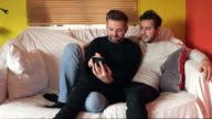 young gay couple looking at mobile phone