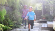 Young girl and boy running and skipping in garden