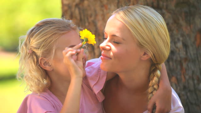 Young girl and her mother playing with a flower / Cape Town, Western Cape, South Africa