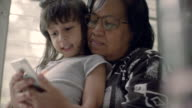 MS Young girl and older woman using smart phone. Thailand