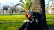 Young girl at 20s relaxing in the park and reading a book II