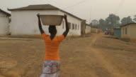 Junges Mädchen Tragen von Wasser auf Ihrem Kopf in African village