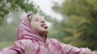 Young girl catching the rain on her tongue