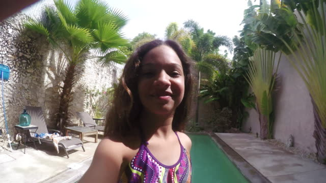 Young Girl Child jumping in the pool and taking selfie
