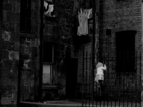 A young girl climbs up metal railings in the Gorbals area of Glasgow