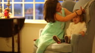 A young girl combing the hair of a toddler baby indoors on a chair.